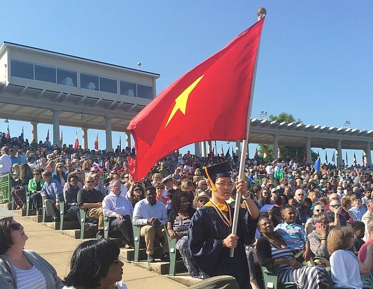 Kỳ thủ Lê Quang Liêm giơ cao lá cờ Việt Nam trong lễ tốt nghiệp tại Đại học Webster (Mỹ). Ảnh: Nhân vật cung cấp