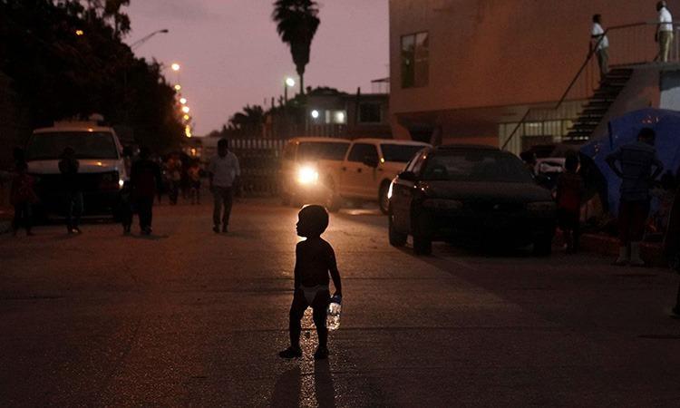 Một đứa trẻ nhỏ đứng tại khu trại tị tạn Matamoros, bang Tamaulipas, Mexico hồi tháng 10. Ảnh: Reuters.
