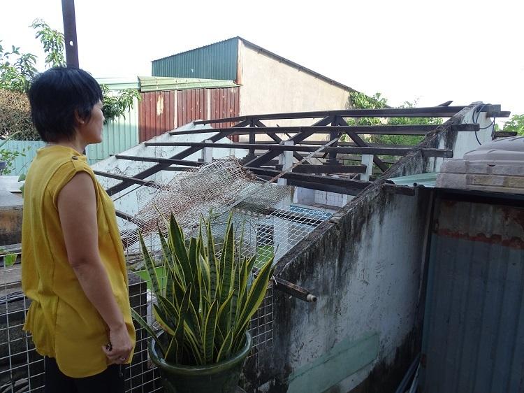 Chị Bình bên căn nhà cấp 4 cũ sắp chìm dần vì lún. Ảnh: Hà An.