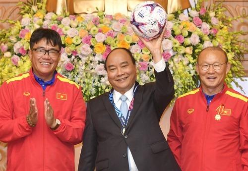 Thủ tướng Nguyễn Xuân Phúc nhận quả bóng đội tuyển VN tặng trong cuộc gặp ban huấn luyện và các cầu thủ ngày 21/12/2018. Ảnh:VGP