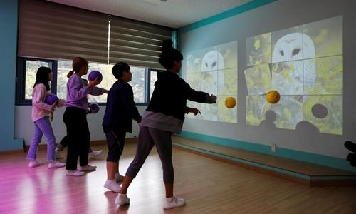 Học sinh chơi trò ném bóng thực tế ảo tại làng Taesung hồi tháng 9. Ảnh: Reuters.
