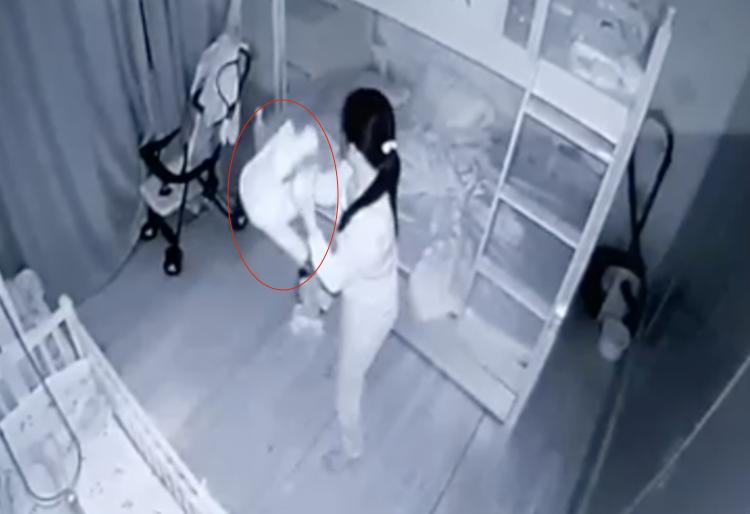 Bé Trâm Anh (vòng tròn đỏ) lúc bị người giúp việc dốc ngược. Ảnh: Cắt từ camera an ninh.