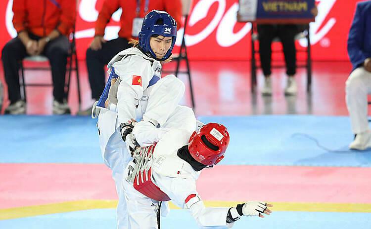 Ánh Tuyết (xanh) áp đảo đối thủ Indonesia ở chung kết hạng 53 kg nữ môn taekwondo. Ảnh: Lâm Đồng.
