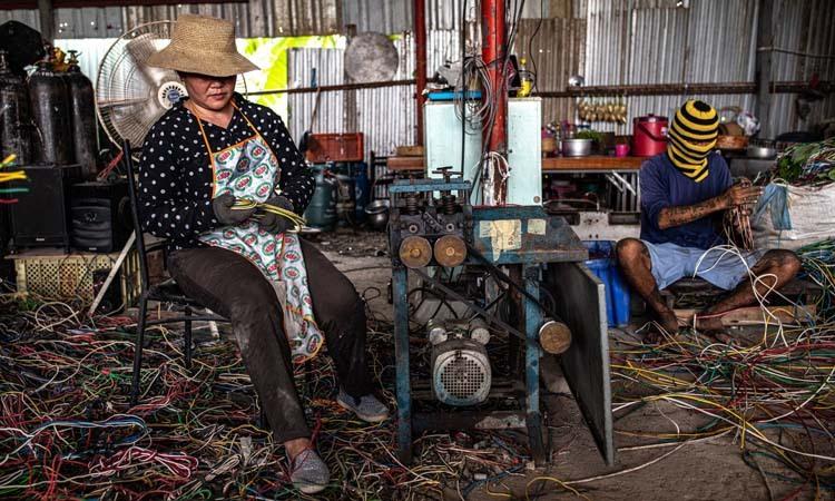 Các công nhân lấy đồng trong các đoạn dây tại một cơ sở ở ngoại ô Bangkok. Ảnh: NY Times.