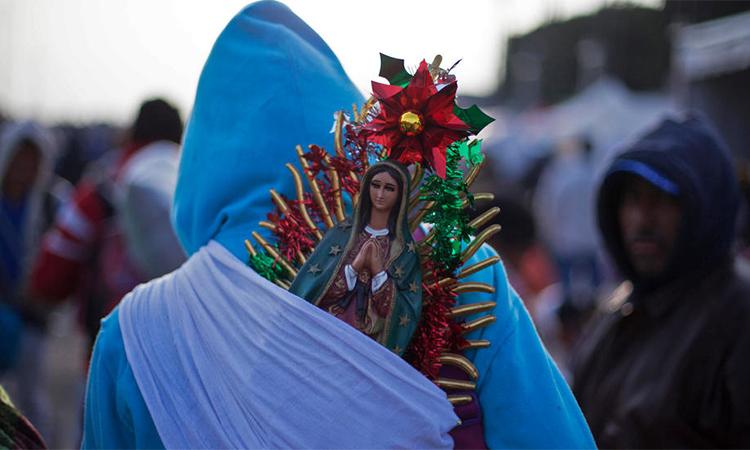 Một người mang theo tượng Đức Trinh nữGuadalupe hành hương về Mexico City ngày 12/12. Ảnh: AFP.