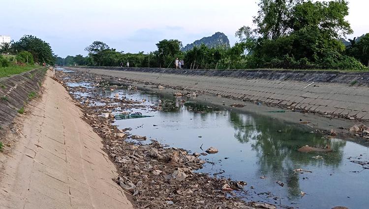 Những ngày cạn nước, đáy kênh Bắc lộ ra dòng nước đen kịt với nhiều loại bùn thải. Ảnh: Lê Hoàng.