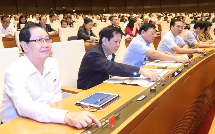 Đại biểu bấm nút biểu quyếtthông qua luật tại Quốc hội. Ảnh:Ngọc Thắng