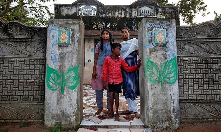 Saranya (bên phải) đứng cùng hai em bên ngoài ngôi nhà ở thị trấn Nagapattinam, bang Tamil Nadu, Ấn Độ, hôm 4/12. Ảnh: Reuters.