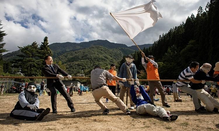 Dân làng Nagoro chơi kéo co bên cạnh những con búp bê tại lễ hội thể thao trường học được tái hiện lại. Ảnh: NYTimes.