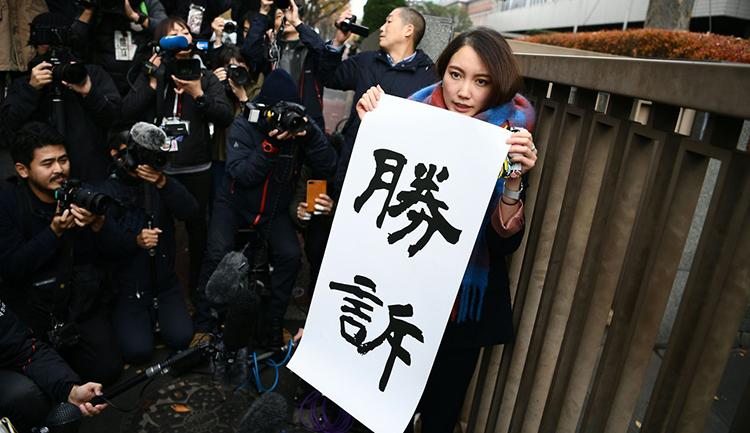 Ito cầm biểu ngữ Thắng kiện trước vòng vây của báo chí. Ảnh: AFP