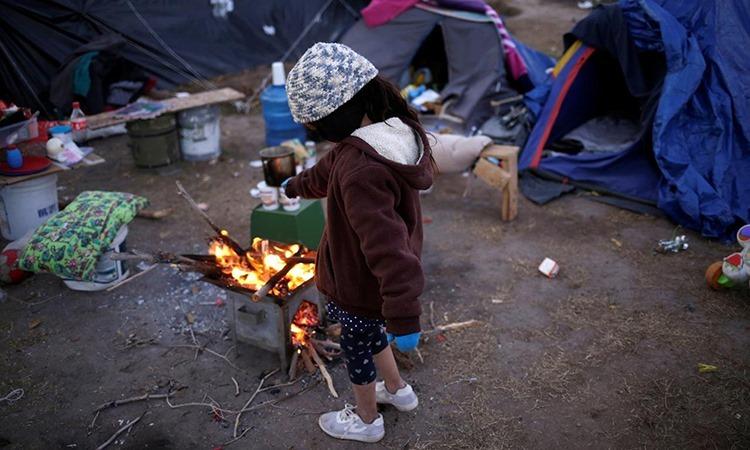 Bé gái Mexico đứng bên bếp lửa tại khu lều tạm ở thành phố Ciudad Juarez, bang Chihuahua hôm 18/12. Ảnh: Reuters.