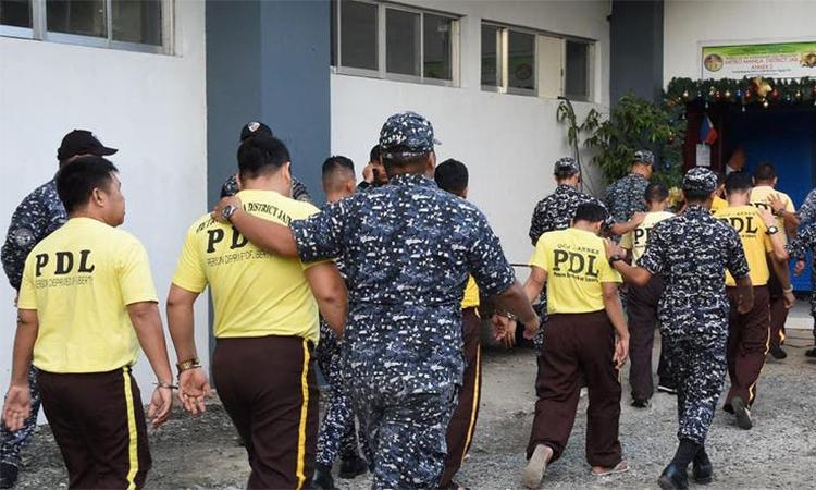 Các bị cáo trong vụ thảm sát Maguindanao (áo vàng) bị cảnh sát dẫn giải đến tòa án ngày 19/12. Ảnh: Reuters.