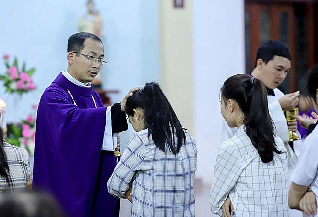 Linh mục Vinh Sơn Vũ Văn Nguyện đặt tay chúc bình ancho một người ngoại đạo đến dự thánh lễ trước Giáng sinh. Ảnh: Nguyễn Đông.