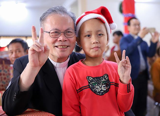 Đức Tổng Giám mục Giuse Nguyễn Chí Linh - Chủ tịch Hội đồng Giám mục Việt Nam chụp hình vui nhộn cùng một em nhỏ trong buổi tặng quà. Ảnh: Nguyễn Đông.