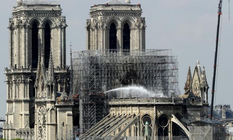 Lính cứu hỏa phun nước dập tắt ngọn lửa trong vụ cháy Nhà thờ Đức bà Paris hồi tháng 4. Ảnh: CNN.