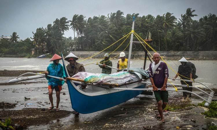 Ngư dân tại thành phố Baybay, tỉnh Leyte, Philippines đưa thuyền lên vị trí cao hơn để tránh bão hôm nay. Ảnh: AFP.