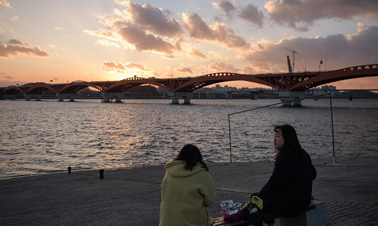 Hai cô gái ngồi bên bờ sông Hán ở Seoul, Hàn Quốc. Ảnh: AFP.