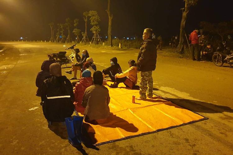 Tối 23/12, người dân rải chiếu giữa đường chặn xe vào cổng số 2 bãi rác Nam Sơn. Ảnh: P.Đ.