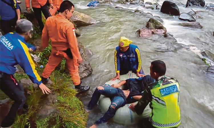 Lực lượng cứu hộ làm nhiệm vụ tại hiện trường tai nạn xe buýt ở Nam Sumatra hôm 24/12. Ảnh: AFP.