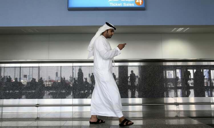 Một người đàn ông dùng điện thoại tại thành phố Dubai, UAE. Ảnh: AP.