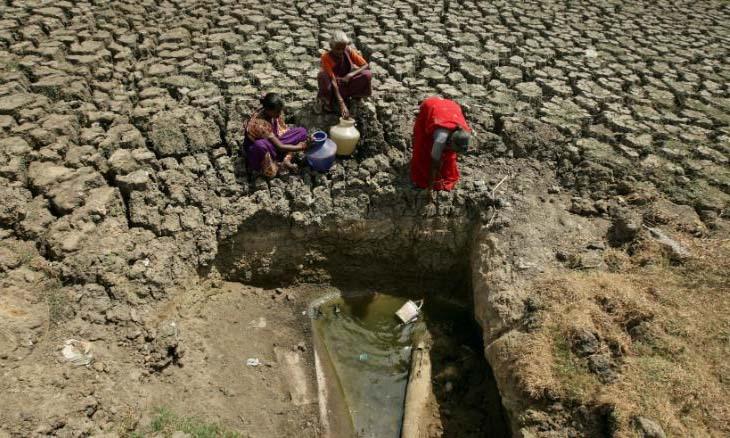 Người dân múc nước từ hố được mở trên một hồ cạn ở thành phố Chennai, Ấn Độ hôm 11/6. Ảnh: Reuters.