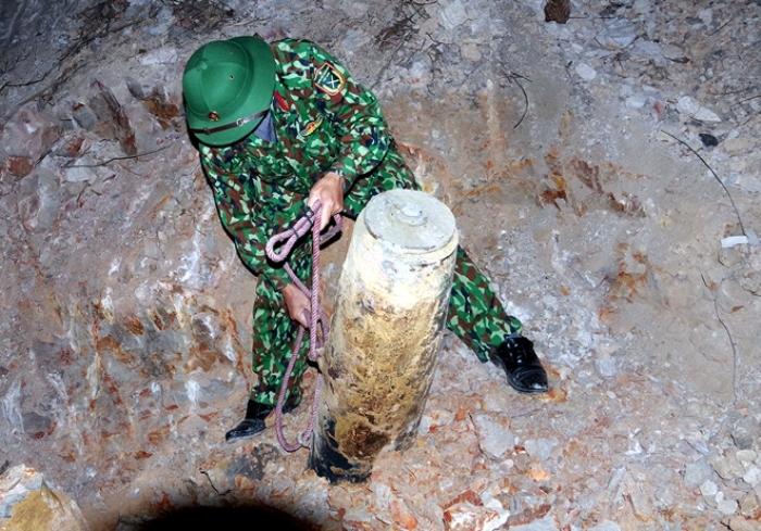 Qủa bom được phát hiện trong tư thế cắm thẳng dưới lòng đất. Ảnh: Phạm Hà