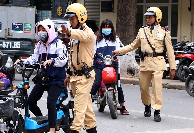 Cảnh sát giao thông Hà Nội trong một lần xử phạt người đi xe đạp điện vi phạm giao thông. Ảnh. Phương Sơn