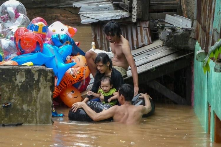 Một gia đình di tản sau trận lụt ở Jakarta sáng 1/1. Ảnh: AFP.