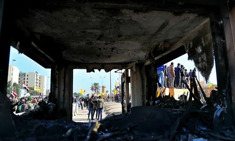 Trạm gác trước đại sứ quán Mỹ tại Baghdad, Iraq, bị đốt cháy và đập phá hôm 1/1. Ảnh: AP.