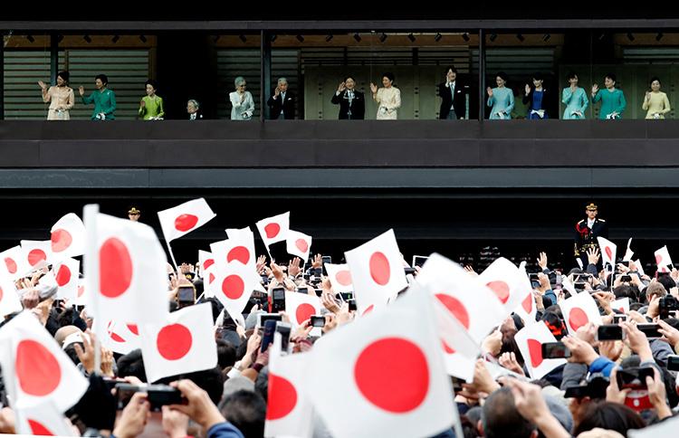 Nhật hoàng (thứ bảy từ trái sang) cùng các thành viên hoàng gia Nhật Bản vẫy chào người dân từ ban công hoàng cung ở Tokyo sáng nay. Ảnh: Reuters