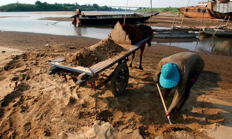 Một người thu gom cát dọc sông Mekong tại tỉnh Kandal, Campuchia hồi năm 2010. Ảnh: Reuters.