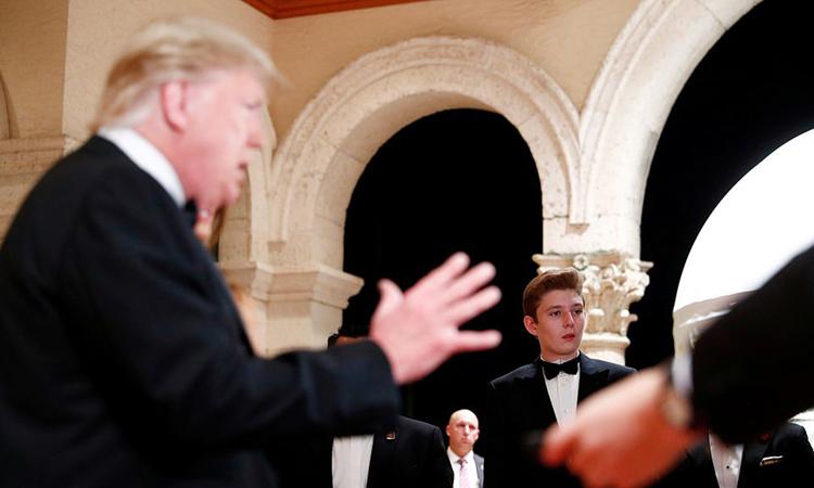 Barron Trump (phải) đứng ở cánh gà khi người cha Tổng thống trả lời báo giới tại bữa tiệc năm mới ở khu nghỉ dưỡng Mar-a-Lago hôm 1/1. Ảnh: Reuters.