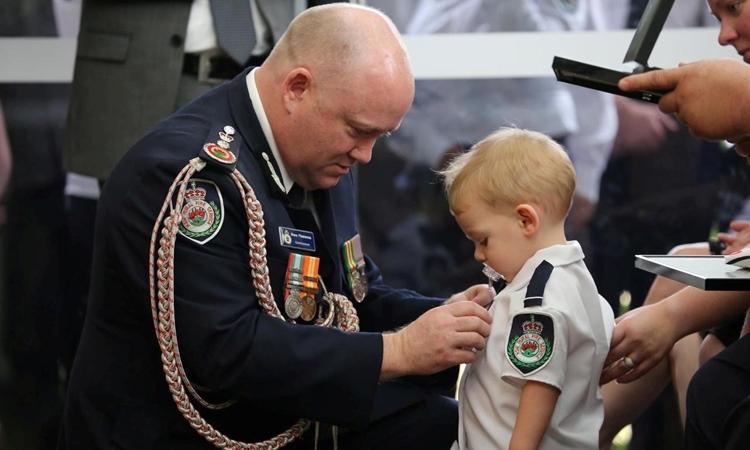 Harvey Keaton, con trai của lính cứu hỏa đã khuất, được Ủy viên Shane Fitzsimmons trao huân chương danh dự trong buổi tang lễ ở Buxton, Australia, hôm nay. Ảnh: Reuters.