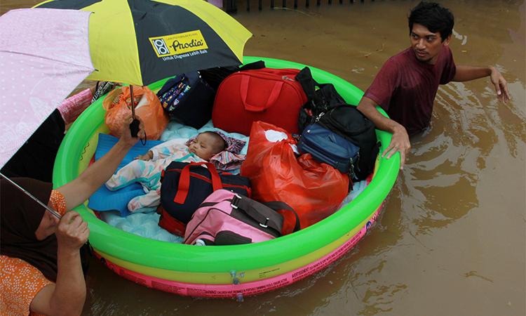 Một em bé được cứu hộ sơ tán bằng phao cứu sinh ở Tangerang, gần Jakarta hôm 1/1. Ảnh: Reuters.