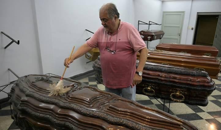 Ông Juan Tapia phủi bụi trên những quan tài bày bán tại nhà tang lễ Cocheria Tacuari ở Buenos Aires. Ảnh: AFP