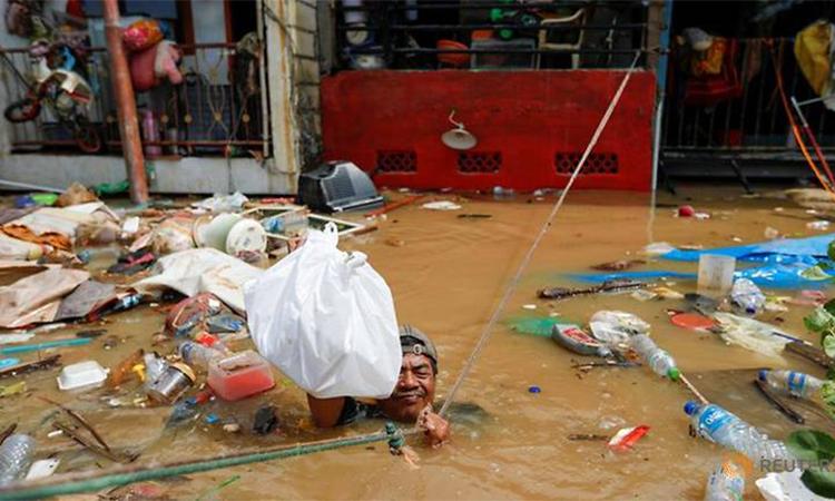 Người đàn ông bám vào dây thừng để phân phát thực phẩm cho nạn nhân vùng lũ ở Jakarta hôm 2/1. Ảnh: Reuters.