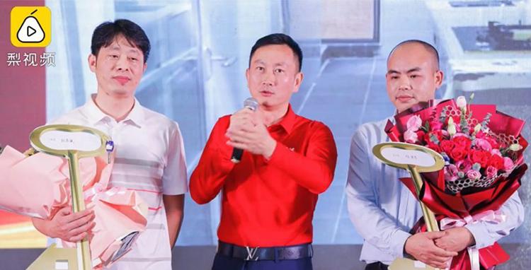 Lãnh đạo công ty ở Đông Quan, Quảng Đông (giữa) tuyên bố thưởng hai nhân viên hai căn hộ trị giá hai triệu tệ. Ảnh: Pear Video