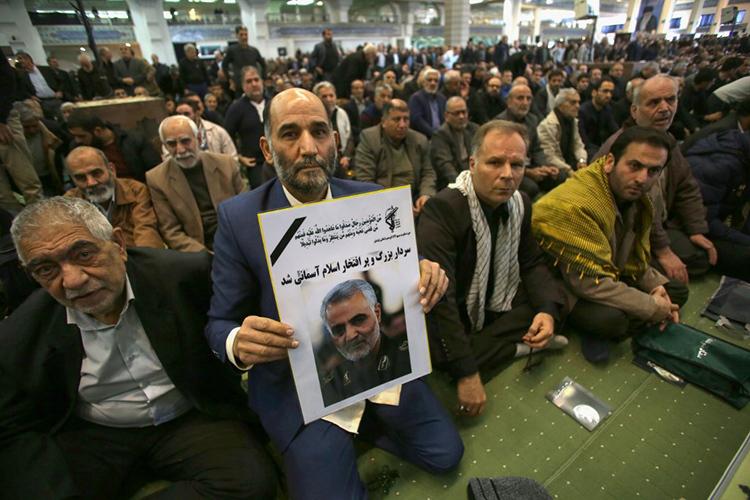 Một người Iran cầm ảnh tướng Qasem Soleimani trong lễ cầu nguyện cho ông tại thủ đô Tehran hôm 3/1. Ảnh: AFP