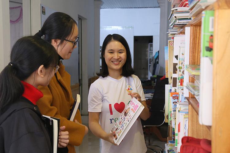 Chị Phương (phải) giới thiệu cuốn sách tiếng Nhật đến hai bạn nữ sinh lớp 12. Ảnh: Hoàng Táo