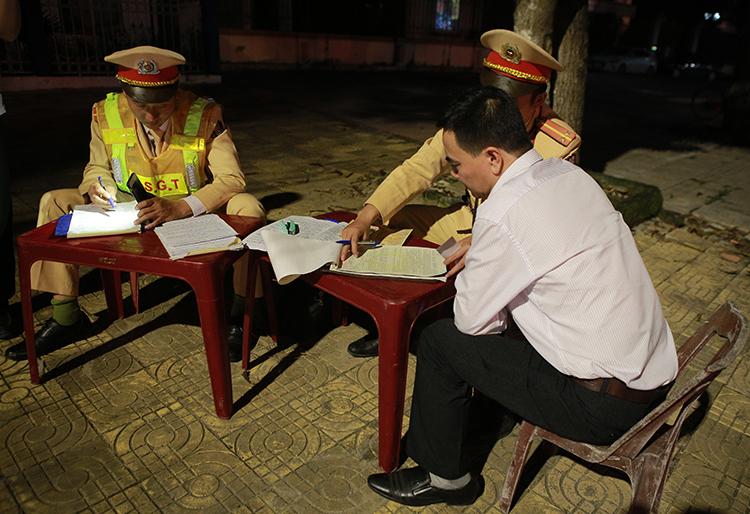Nam tài xế được yêu cầu ký vào biên bản vi phạm. Ảnh: Nguyễn Hải.