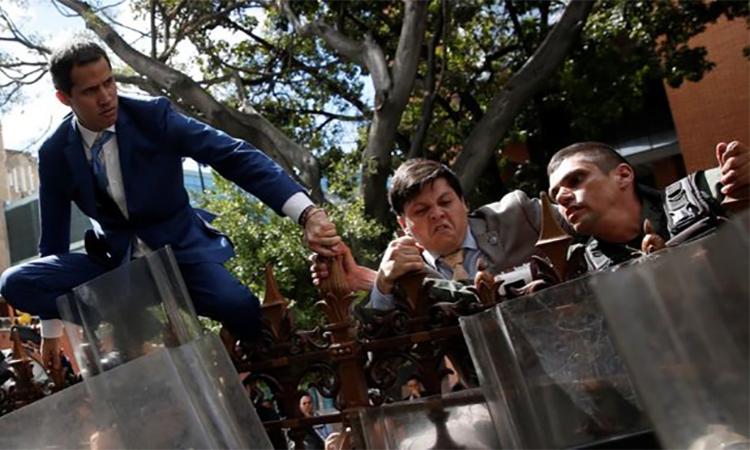 Thủ lĩnh đối lập Venezuela Guaido (trái) trèo hàng rào để vào quốc hội hôm 5/1. Ảnh: Reuters.