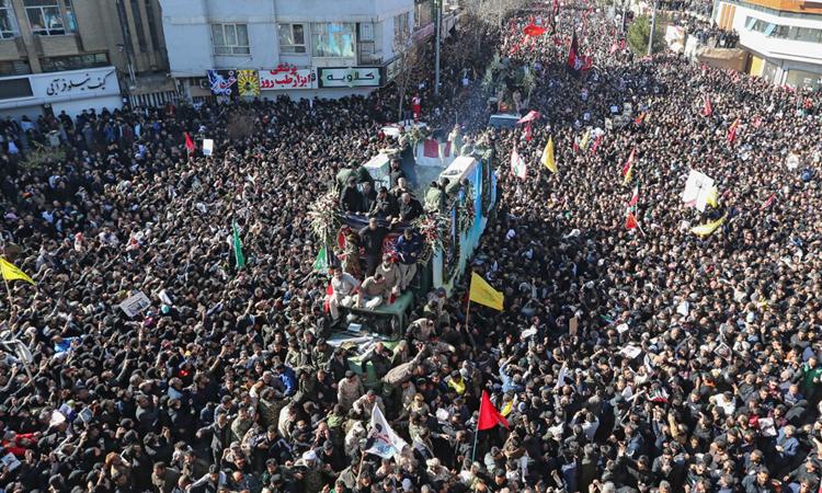 Người dân vây quanh xe chở linh cữu tướng Soleimani trong tang lễ tại Kerman hôm nay. Ảnh: AFP.