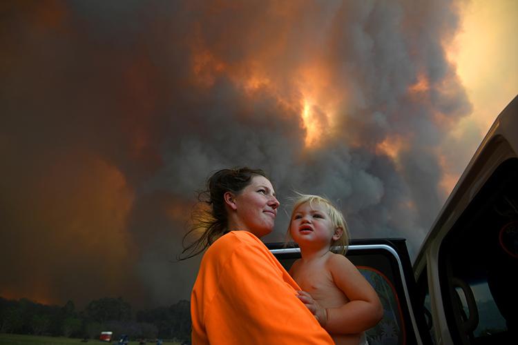 Sharnie Moren và con gái Charlotte, 18 tháng tuổi, đứng giữa làn khói bốc lên ngùn ngụt gần làng Nana Glen, bang New South Wales, Australia hồi tháng 11/2019. Ảnh: Reuters