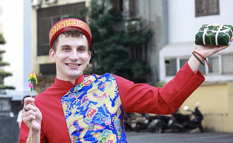 Elijah vui mừng nhận hai món quà là tò he và bánh chưng khi tham gia chương trình Tết Việt sáng 9/1. Ảnh: Dương Tâm