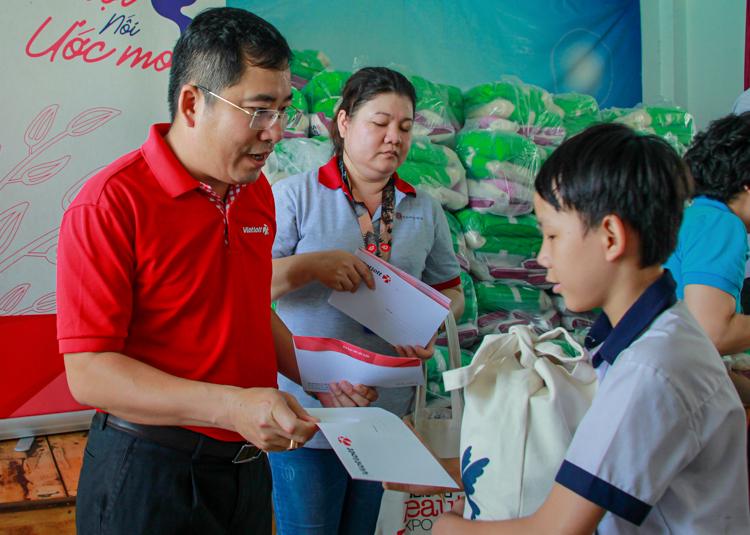 Ông Ngô Ngọc Ân, đại diện Vietlott (trái) trao quà Tết cho các em học sinh tại Trường tình thương Thiên Ân. Ảnh: Thanh Trần