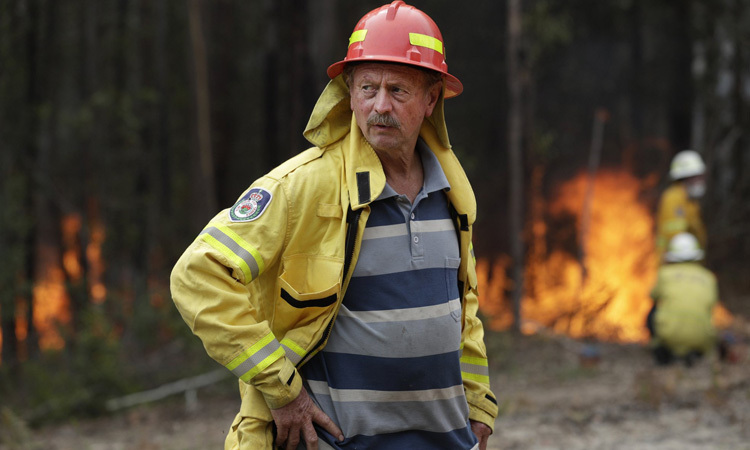Doug Schutz đứng quan sát đám cháy có kiểm soát ở Tomerong, NSW hôm 8/1. Ảnh: AP.