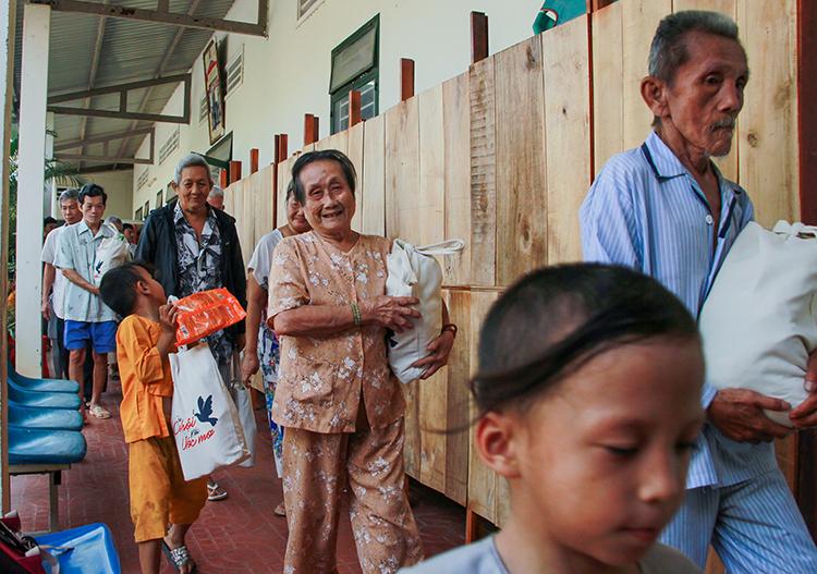 Những cụ già, em nhỏ tại Mái ấm Mây Ngàn phấn khởi nhận quà Tết. Ảnh: Thanh Trần