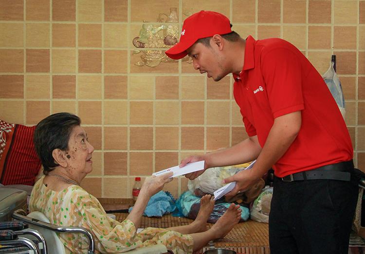 Đại diện Vietlott trao quà Tết cho từng cụ già ở Mái ấm Mây Ngàn. Ảnh: Thanh Trần