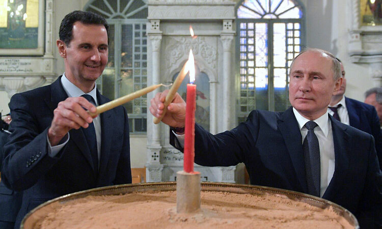 Putin (phải) và Assad thắp nến tại nhà nguyện ở Damascus hôm 7/1. Ảnh: AP.