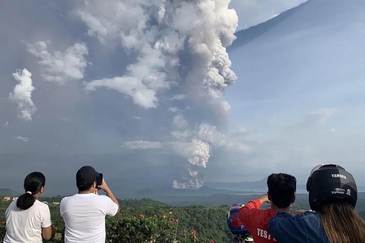Người dân chụp ảnh núi lửa Taal từ thành phố Tagaytay, phía tây nam thủ đô Manila. Ảnh: AFP.